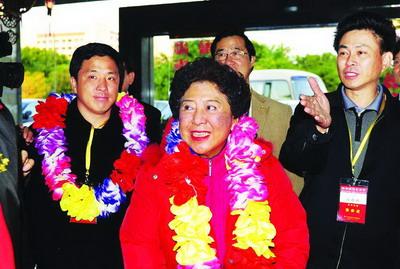 孙穗芳母子戴上欢迎的花环。右一为新加坡孙氏公会主席孙嘉和。