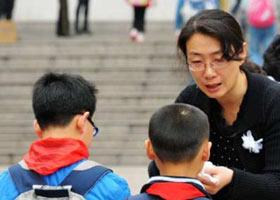 老师在学校门口向学生发放小白花