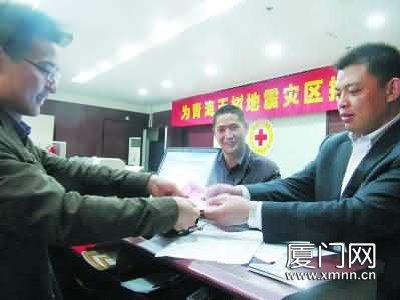 15日,一名男子带着7名同事的捐款,冒着大雨来到市红十字会捐款。吴俊鸿 摄