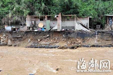 被山洪冲毁路基的民房悬在山腰上