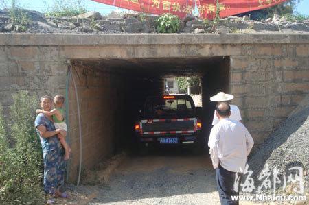涵洞狭小,有车经过时村民只能在洞口等待