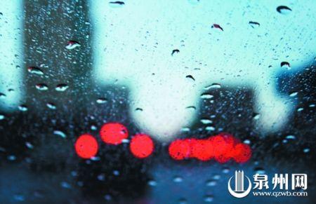 透过汽车挡风玻璃可以看到,车辆的尾灯在雨幕中形成一道别样的风景.