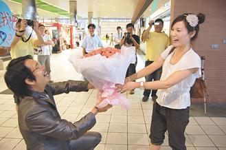 男生庄胜杰在高铁桃园站大厅,捧花下跪向女友谢欣燕求婚,让谢女惊喜不已。台湾《联合报》图