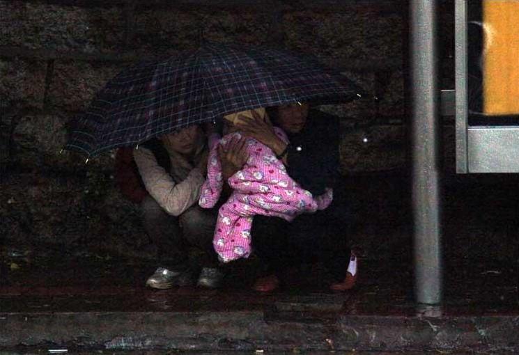 厦门:两名市民在避雨