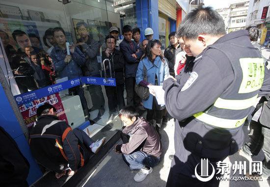 小偷(蹲地上者左一)被见义勇为的男子追到当场抓住,在一旁直抖腿的小偷老乡(蹲地上者左二)也被暂时控制。
