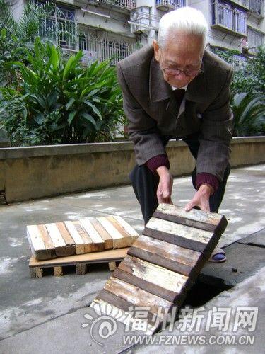 林老伯正在用自制的木板修补小区地沟