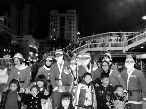 """几个""""圣诞老人""""和市民在天桥前合影"""