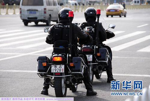 3月1日,特警队员在人民大会堂东门外巡逻。十一届全国人大第四次会议、全国政协十一届四次会议即将开幕。新华网 孙巍 摄