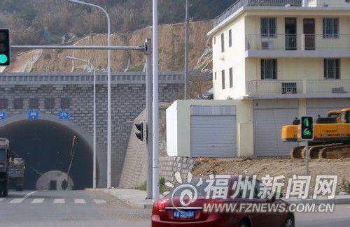 隧道入口处一侧护坡与附近房子之间,新砌了约一层高的围墙,还安装了卷帘门