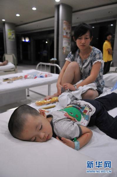 7月24日凌晨,在温州市康宁医院内,一位乘坐D301次列车的乘客望着病床上熟睡的孩子。新华社记者 鞠焕宗 摄