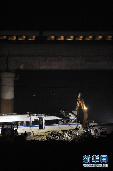 7月25日,挖掘机正在对事故列车车厢进行拆解,运行列车从上方经过。新华社记者徐昱 摄