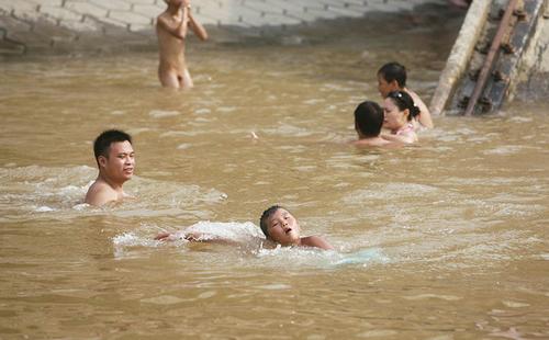 天气炎热,市民在江里戏水避暑。