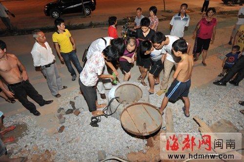 听说有小孩掉入水井,周边的居民忙带上手电筒前来探个究竟