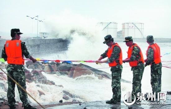昨日中午,在晋江深沪商业码头,边防官兵正在临时绑设安全绳和防护栏。 (陈英杰 摄)
