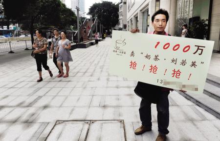 男子举牌在街头叫卖