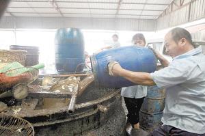 """正规企业工作人员将""""地沟油""""倒入罐内加热进行油水杂质分离。常海军 摄"""