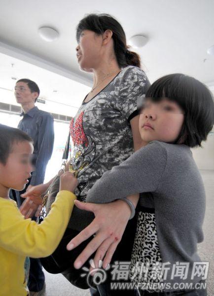 惊魂未定的女孩(右)紧紧抱着母亲。