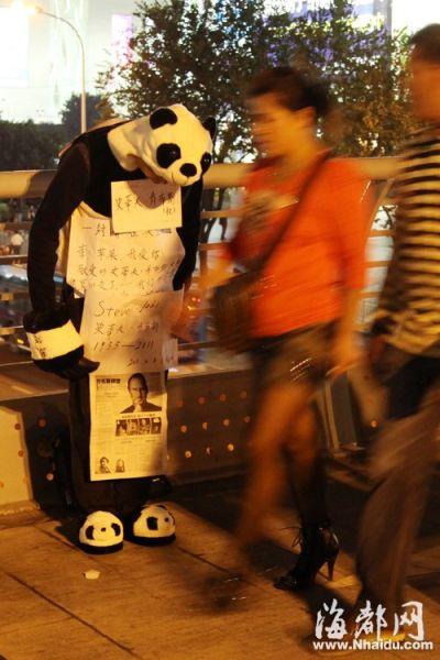 """名男子身穿""""熊猫""""装,站在福州宝龙城市广场前的人行天桥上"""