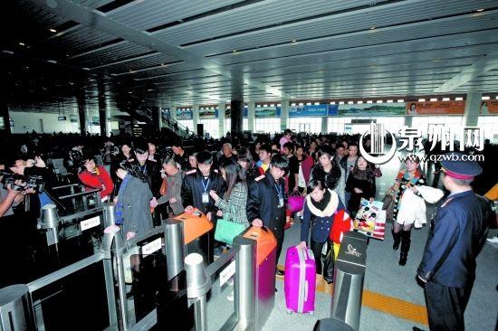 昨日,高铁泉州站工作人员正指导乘客刷二代证上车。
