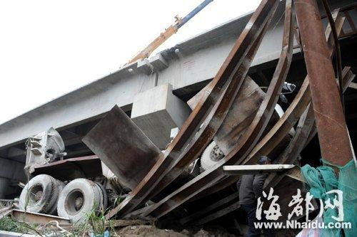 一辆水泥搅拌车从引桥旁的钢便桥(注:用于工程的钢结构工具桥)上坠落