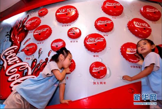 7月4日,在北京可口可乐有限公司的博物馆内,两名小朋友试听世界各地可口可乐发音。 新华社记者 陈建力 摄