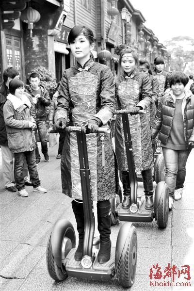 美女巡游队身着古装,骑着帅气的独轮车,成为南后街又一道风景