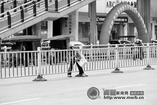 """在龙腾路家和天下路段的人行天桥底下,一位阿婆冒险""""穿""""过隔离栏。"""