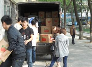 学生们把成箱的脐橙搬上运输车