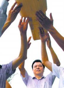 城建项目团队负责人吴长树带领团员们冲在建设一线亲力亲为,图为他和大伙合力为仿古戏台上大梁。