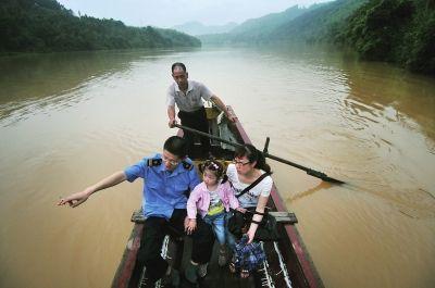 站长张永建的妻子和女儿利用休息时间坐着小船到车站看望他