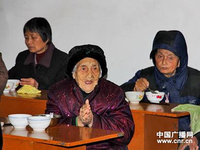 这位近百岁的老人向记者合十致意。(图片来源:中国广播网)
