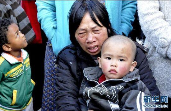 9月16日,在南非自由州省沃登地区,受害人陈荣梁的母亲悲痛地抱着幸存的三岁孙子。