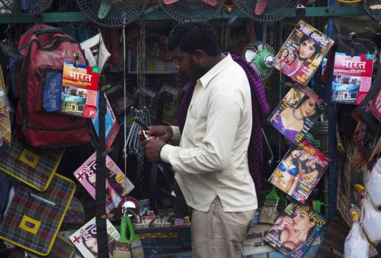 一名印度商人从成年杂志报摊前经过。