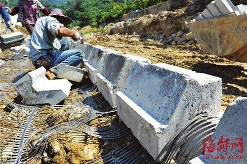 钟潭溪,砖块与砖块之间并没有用任何固定的材料,每三层生态砖上都铺设一块土工网
