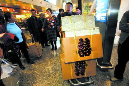 昨日,江北机场,新娘的父亲推着满载礼物的行李车从机场出来 记者 钟志兵 摄