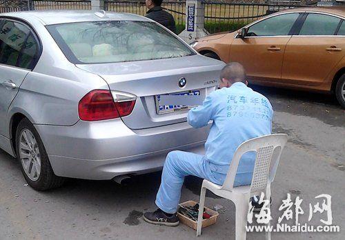 工人在拆除小车的车牌框