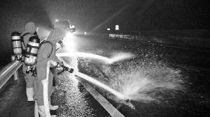 消防官兵正在出水冲击路面上的化学分解物。