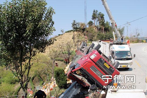 事故现场,施救车辆正在施救侧翻的货车。