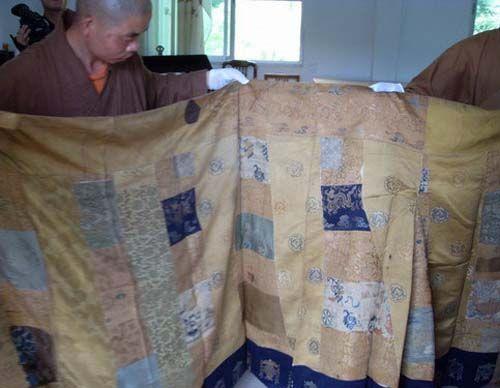 图为僧人展示云锦五爪金龙紫衣袈裟。