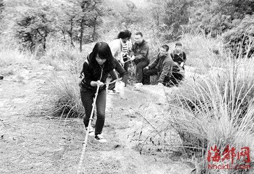 在搜救队员的帮助下,三名迷路少女爬上悬崖