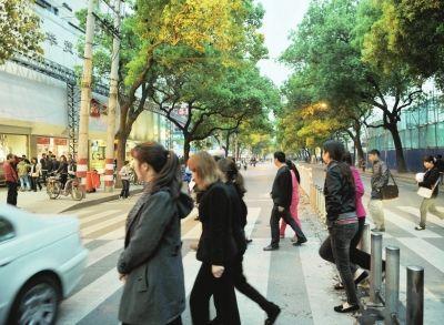 24日,一群逛街行人从南街斑马线经过