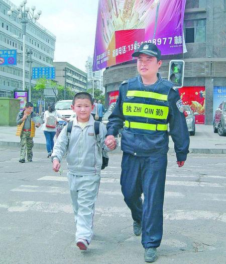 李优文在交通重点整治区域――永安汽车站红绿灯十字路口护送小学生