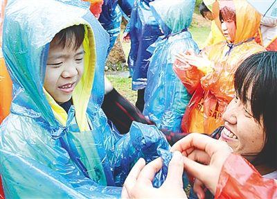 爱心妈妈为孤残儿童穿雨衣