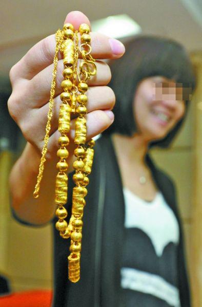 昨日,江北区花园村派出所,杨女士拿着黄金首饰讲述自己收到包裹时的情景。记者 吴珊 摄
