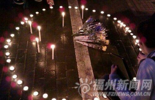 学生在事发地点起蜡烛纪念逝去的老师