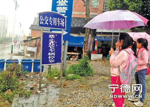 24日下午5时15分,3名放学的孩子站在1路公交原硕丰蔬菜批发市场站点旁,该站点虽已停用,但公交站牌仍未拆除。赵 琼 摄