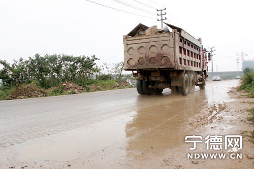 载满石块的土方车行驶在路上。