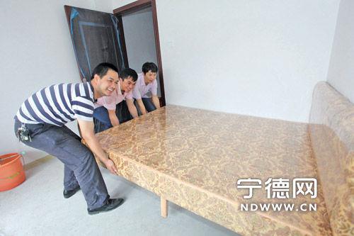 卢新元和工友们一同整理新房,置放家具。