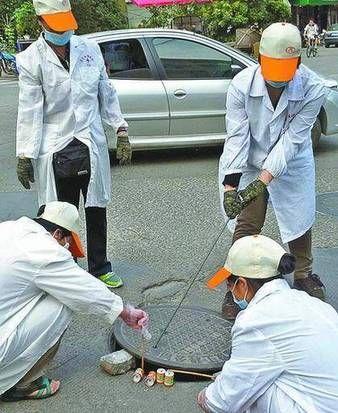 卫生消毒站工作人员在市区对各下水道进行灭蚊、除蟑