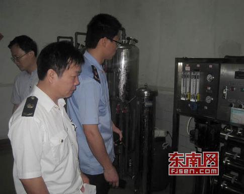 执法人员查处桶装水生产黑窝点